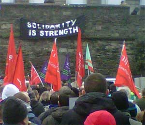 Anarchist banner hangs from city walls in Derry during N30 strike rally